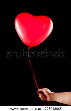 Female hand holds red rubber inflatable heart shape balloon. Love, relationship, valentines day and birthday celebration concept. Studio shot on an abstract blurred background with blank copy space #1278018565