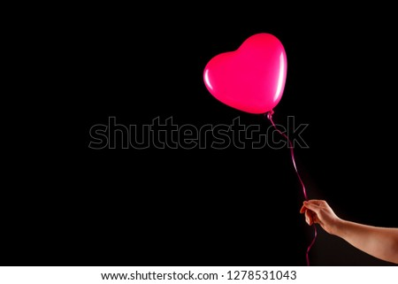 Female hand holds red rubber inflatable heart shape balloon. Love, relationship, valentines day and birthday celebration concept. Studio shot on an abstract blurred background with blank copy space #1278531043