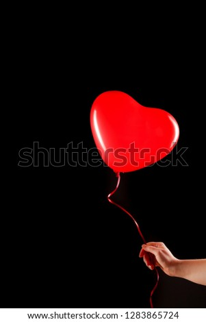 Female hand holds red rubber inflatable heart shape balloon. Love, relationship, valentines day and birthday celebration concept. Studio shot on an abstract blurred background with blank copy space #1283865724