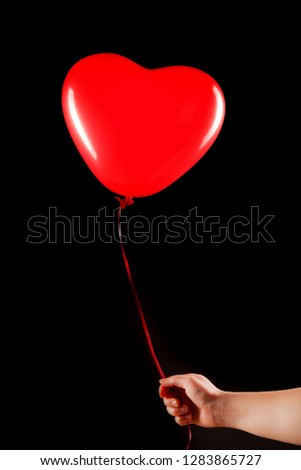 Female hand holds red rubber inflatable heart shape balloon. Love, relationship, valentines day and birthday celebration concept. Studio shot on an abstract blurred background with blank copy space #1283865727
