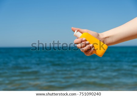 Female hand holds the bottle against a sandy beach and sea in bright Sunny day from right side of frame #751090240