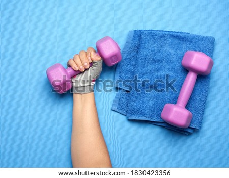 female hand in a pink sports glove holds a purple one kilogram dumbbell on a blue background Stock photo ©