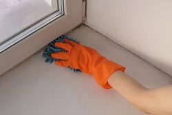Female hand in an orange protective glove with a blue damp rag washes and cleans the window sill from dust and dirt