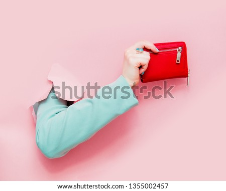 Female hand in classic blue jacket show purse looks out from pink background #1355002457
