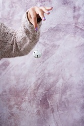 Female hand in cozy pink sweater holding a jingle bell. Christmas decoration concept