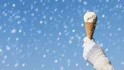 Female hand in knitted gloves with ice cream in a waffle horn on the winter snowfall background. Concept