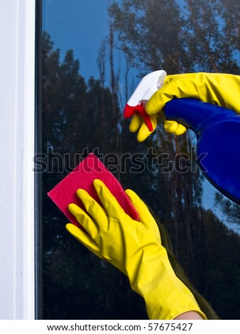 Female hand in pink glove cleaning window with yellow microfibre