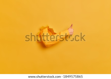Female hand in yellow jumper gestures ok approval sign keeps thumb up recommends something breaks through paper background. Copy space for advertising content. Best choice concept. Hole in wall Foto stock ©