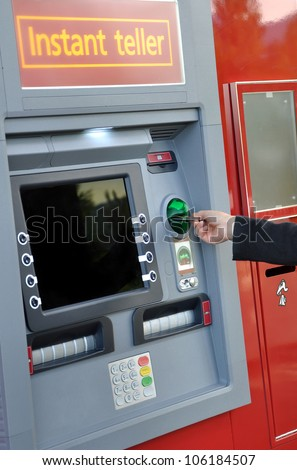 Female hand inserting a bank card at an automatic bank teller machine