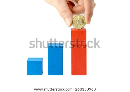 Stock Photo Female hand is holding US dollar coin above red  wooden cube on a white  background. The first cube is blue and low, the second is blue and higher. On the last red cube is added the  US dollar coin.