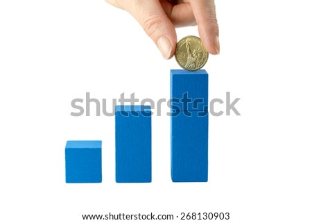Stock Photo Female hand is holding US one dollar coin above blue wooden cubes on a white  background. The first cube is low, the second is higher. On the last blue cube is added the one US dollar coin.