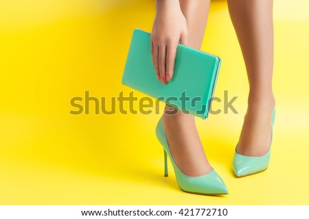 female hand keeps portable turquoise bag on yellow background; sexy woman legs weared in stylish stiletto shoes;