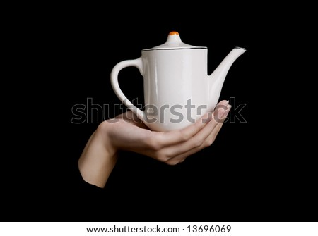 female hand  keeps teapot on black background