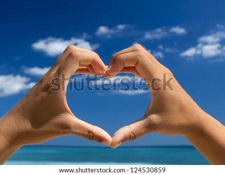 Female hand making a heart shape against a beautiful blue sky
