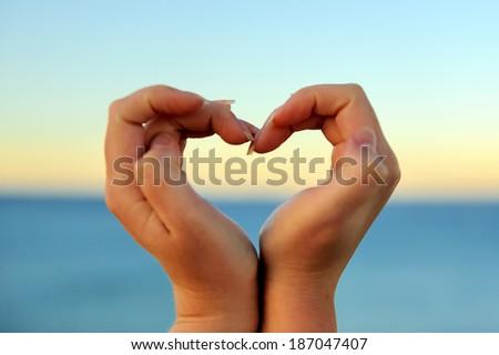 Female hand making a heart shape against a beautiful blue sky