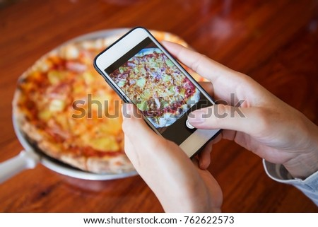 Female hand making a photo of pizza, with a mobile phone, close up, horizontal