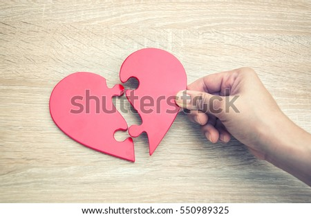 female hand matching red jigsaw heart halves on grey wooden background #550989325
