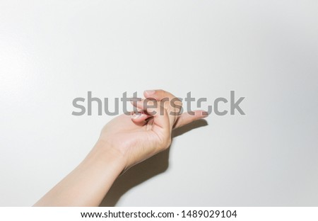 Female hand model posing pointy finger at a potential product, on a clean and simplistic white background.