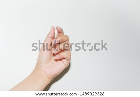 Female hand model with posed, slender, long fingers and beautiful nails; photographed on a gorgeous white background.