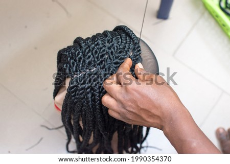 Female hand of Hairdresser making weaves on braids wig on mannequins head, making creative artificial hairstyle and working with scissors, needle and tread  Foto stock ©