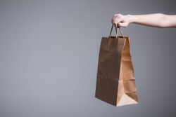Female hand on a gray background holds out or picks up a paper bag with handles. Advertising shooting for a company with delivery