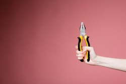 Female hand on a pink background in the studio holds pliers as an advertising banner for a construction store and services.