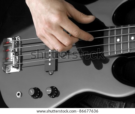 female hand on the detail of a black bass guitar in dark back