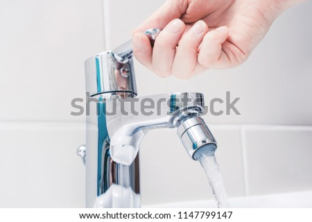 Female Hand On The Handle Of A Chrome Faucet With Running Water