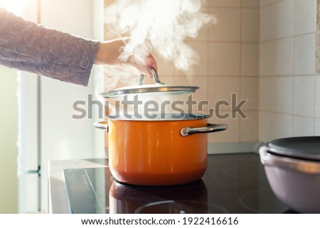 Female hand open lid of enamel steel cooking pan on electric hob with boiling water or soup and scenic vapor steam backlit by warm sunlight at kitchen. Kitchenware utensil and tool at home background