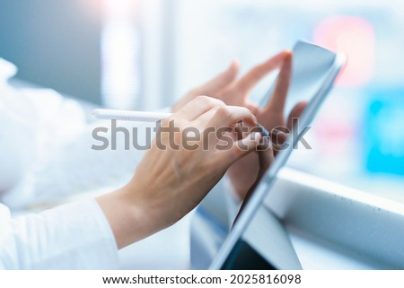 Female hand operating a tablet PC with a stylus pen Foto stock ©