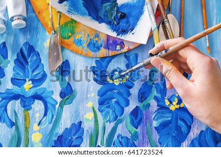 Female hand painting beautiful picture