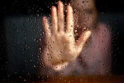 Female hand palm silhouette through behind the window with raindrops reaching for the glass. A request for help, depression, stress blurred bokeh background. Refusal  denial of alcohol and drugs
