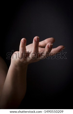 Female hand palm up on a black background #1490550209