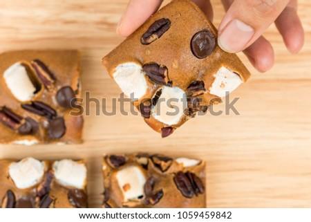 Female hand picking blondies cakes.