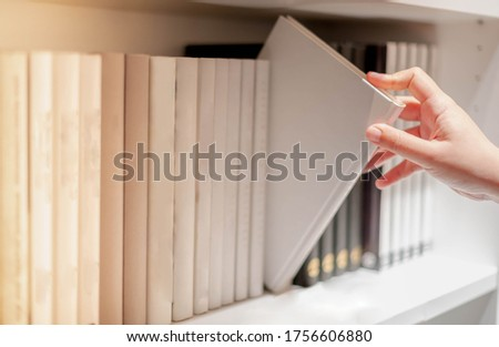 Female hand picking new book on shelf in bookstore shop. Personal information book or magazine for business or education research. Buying office supplies concept Foto stock ©