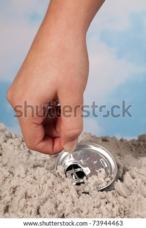 Female hand picking up a discarded soda can on a beach