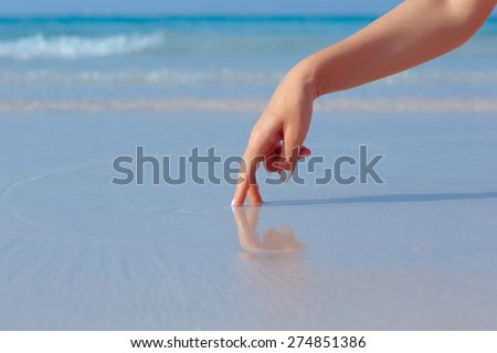 Female hand playing in the water on the white sand beach on blue sea background #274851386