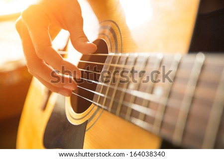 Female hand playing on acoustic guitar. Close-up. #164038340