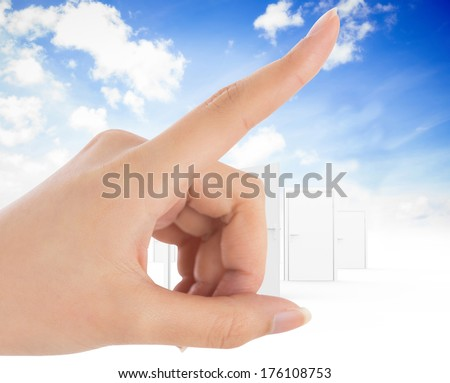 Female hand pointing against opening door in sky