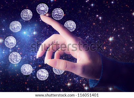 female hand pointing to zodiac signs over starry Universe