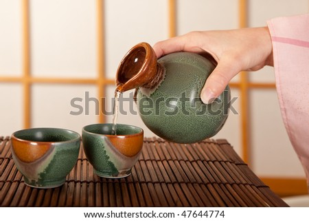 Female hand pouring two cups of japanese sake