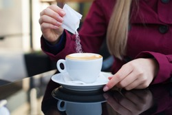 Female hand pours sugar into coffee