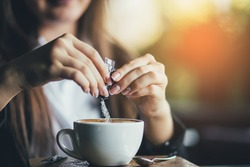 Female hand pours sugar into coffee. Sunlight background
