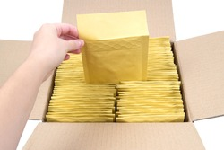 Female hand pulling a shipping envelope out of an opened box full of bubble mailers.