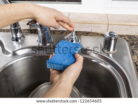 Female hand pushing soap dispenser for soap to put on cleaning sponge with stainless steel sink and pan in background