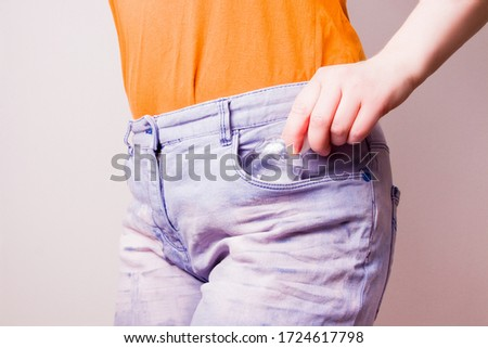 female hand puts a bottle of gel sanitizer in a pocket of blue jeans, copy space, light background Foto stock ©