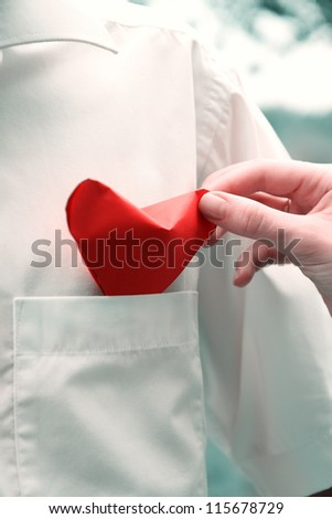 Female hand puts heart into his shirt pocket