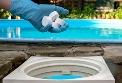 Female hand puts white tablets into pool skimmer. Cleaning, disinfection of water in the swimming pool.