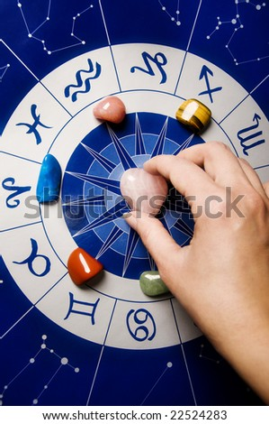 female hand putting a healing stone on an astrological wheel