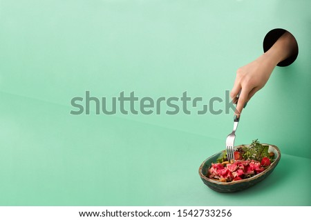 Female hand reaches for Roast Beef Salad through the hole in green wall. Food concept in neo mint colour. Hand takes food through hole. Red beef salad. Copy space